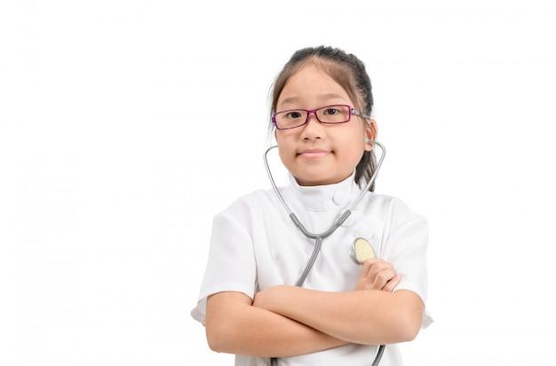 Милый азиатский ребенок в пальто доктора при изолированный стетоскоп