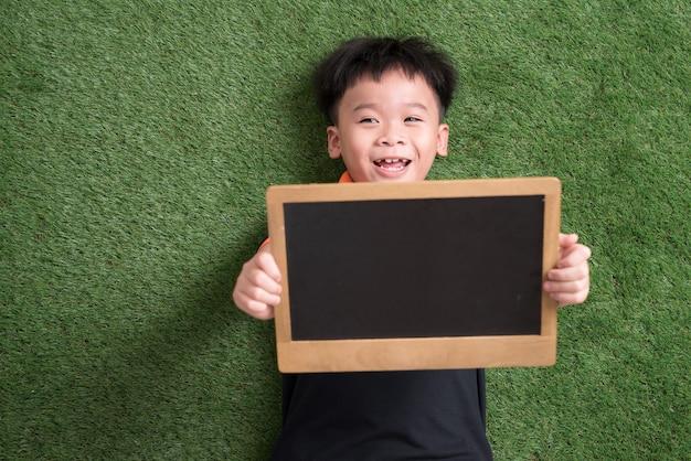 Милый азиатский ребенок лежит и держит доску на зеленой траве