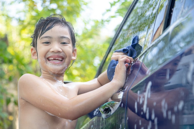 夏の日にホースで車を洗うかわいいアジアの子供