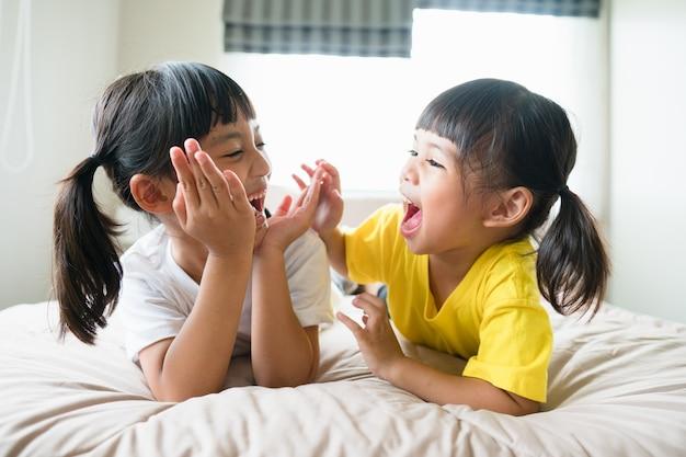 ベッドに横たわっているかわいいアジアの子供たち