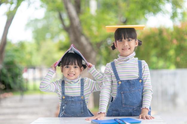 テーブルの上の本を読んでかわいいアジアの子供たち