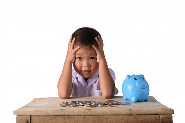 Cute asian country boy have headache with piggy bank and coins isolated on white