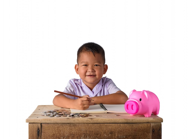 Cute asian country boy make a note of income receipts and coins with piggy bank