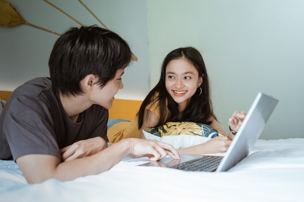 Милая азиатская пара отдыхает на кровати, используя ноутбук дома в спальне вместе