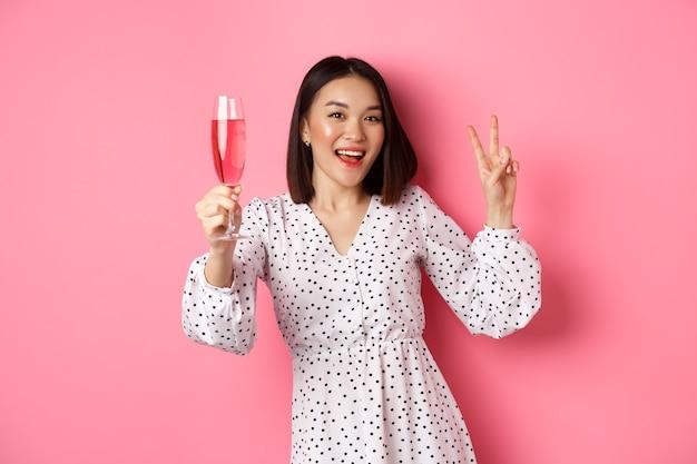 샴페인을 마시고, 파티에 축하하고, 평화 서명을 보여주는 귀여운 아시아 여성 모델, 핑크 위에 서 카메라에 행복 미소.