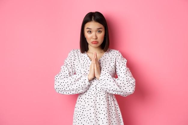 Симпатичная азиатская девушка просит о помощи, умоляет об одолжении и невинно смотрит в камеру, умоляя на розовом фоне