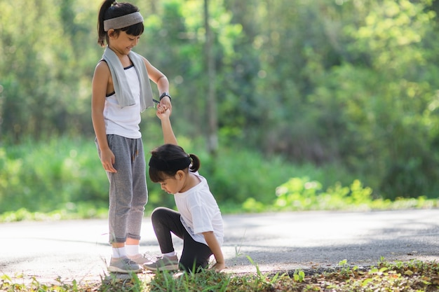 Симпатичная азиатская девушка протягивает руку, чтобы помочь сестре в аварии во время бега