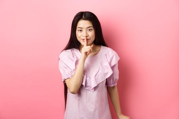 Симпатичная азиатская девушка, скрывающая секрет, замолкает, прижимая палец к губам и улыбаясь, прося молчать, стоя в платье на розовом фоне.