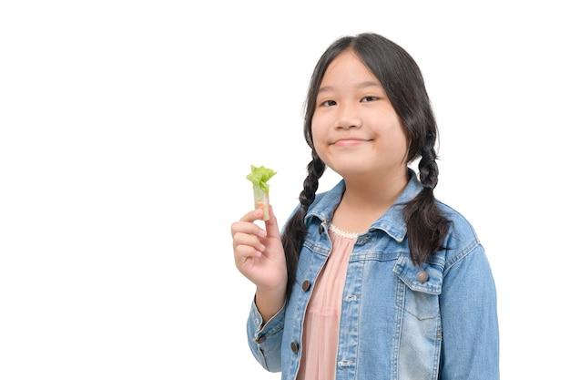 귀여운 아시아 소녀는 흰색 배경, 건강 식품 및 다이어트 개념에 격리된 태국 샐러드 롤을 들고 있습니다.