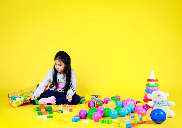 Симпатичная азиатская девочка сидит в одиночестве и любит играть, собирая пластиковый блок, чтобы тренировать мозг для творчества и логики, на полу, полном разнообразных красочных игрушек, таких как мяч, обруч, милый плюшевый мишка