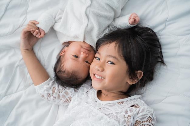 彼の赤ん坊の弟と一緒にベッドの上に敷設かわいいアジアの女の子
