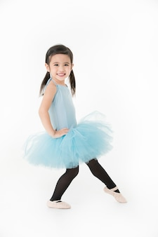 Cute asian girl in light blue dress preforming ballet with smiling face, isolated
