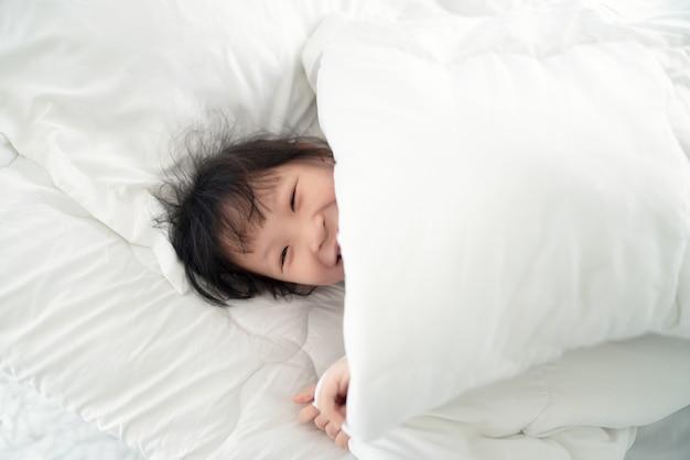 흰색 침대에 담요 아래 누워 귀여운 아시아 여자
