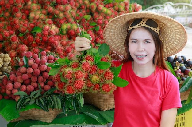 かわいいアジアの女の子の商人、彼女の果物。