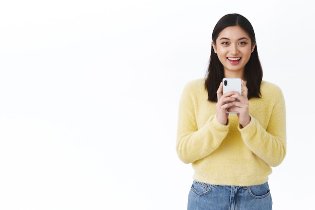 Cute asian girl photographer taking shot of friend on mobile phone, smiling happy, record video using smartphone, standing white wall internet blogger stream online