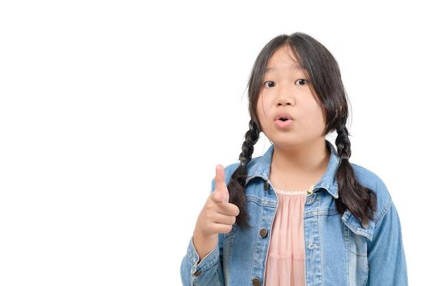 Симпатичная азиатская девушка указывает пальцем на камеру и делает шокированное выражение на белом фоне. концепция эмоций