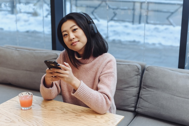A cute asian girl sits in a coffee shop, listens to music in large bluetooth headphones and drinks freshly squeezed juice. beautiful adult girl enjoys music in a public place