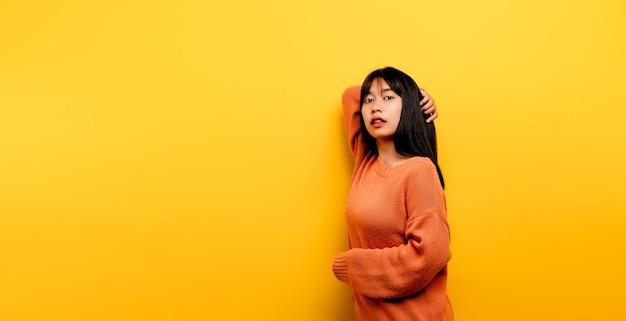 Симпатичная азиатская девушка улыбается на желтом фоне. пустая, молодая женщина. место для рекламы. копировать пространство