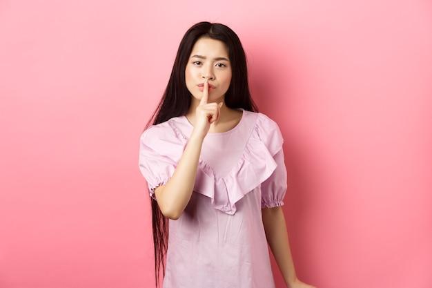 かわいいアジアの女の子は静かで、大声で叱り、ピンクの背景にドレスを着て立っている、唇に指を押してshushサインを示していると言います。