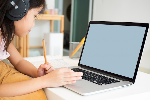 Cute asian girl use notebook computer for studying online lesson during home quarantine.