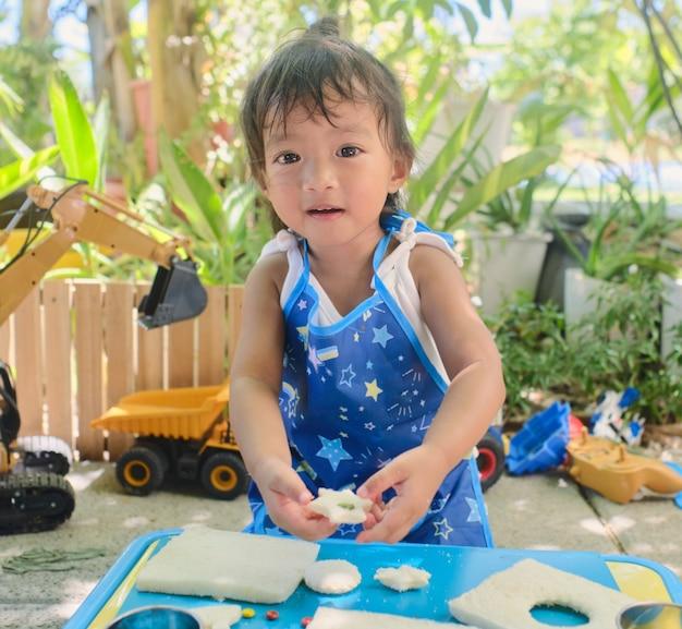 家でクッキーカッターサンドイッチを準備したり作ったりするのを楽しんでいるエプロンを着ているかわいいアジアの女の子