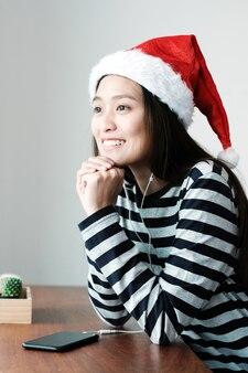 Симпатичная азиатская девушка в шляпе рождество и прослушивания музыки