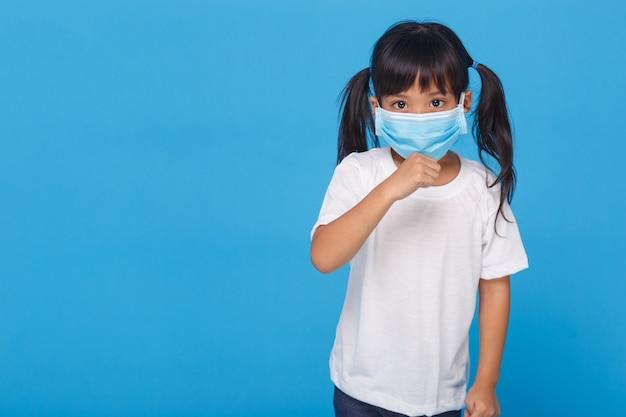 マスク咳を着てかわいいアジアの女の子