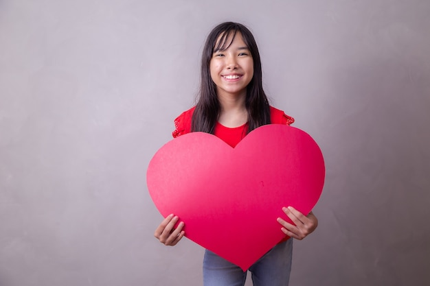 テキスト用のスペースを持つ巨大なハートカードを持つかわいいアジアの女の子。