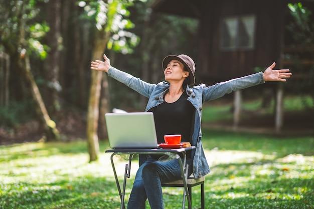 丘の自然に休暇の休日の時間にテーブルでコーヒーを飲みながら働くかわいいアジアの女の子