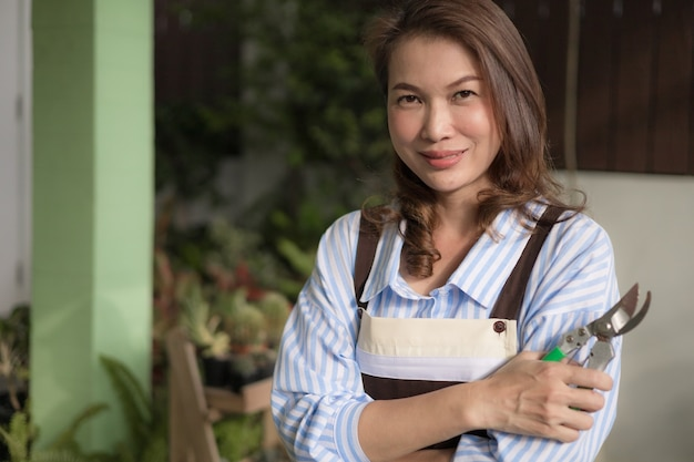 Cute asian housewife wearing apron holding pruning shears cross hands and looking to camera ready to cut and prune leaves and branches of small tree in house backyard. hobby for woman concept.