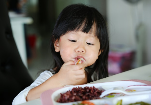 Cute asian kid girl age about 2 years old eating rice by self