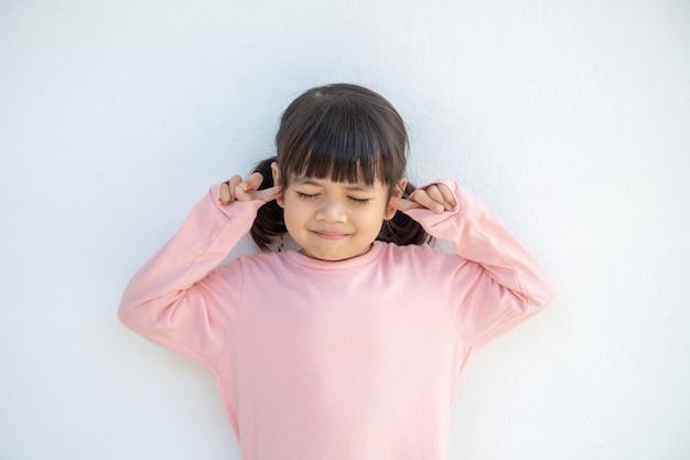 Симпатичная азиатская девочка закрыла уши пальцами и жестикулировала, что не хочет слушать, на белом фоне с пустым пространством для копирования