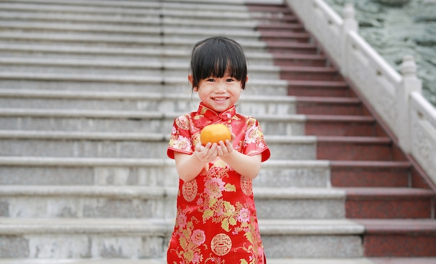 Cute asian kid girl in traditional chinese dress with holding sacred orange at chinese temple
