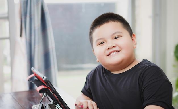 自宅のタブレットからオンラインでクラス学習を学ぶかわいいアジアの子供。社会距離の概念