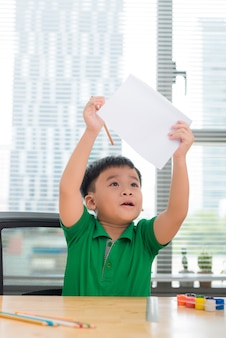Cute asian kid sit at the table with colorful folders and draws with pen, hold paper painting.