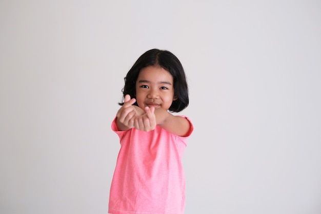 Cute asian kid smiling while giving love finger symbol