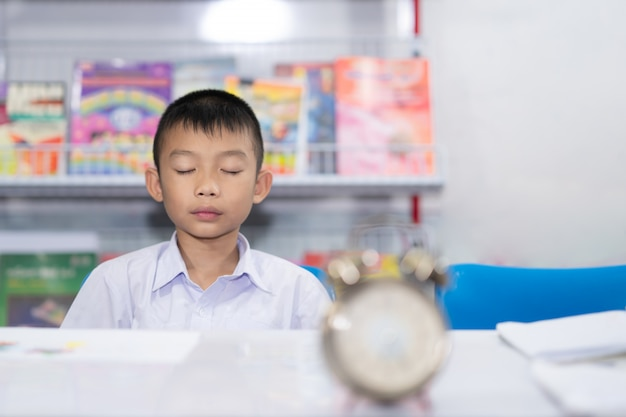 Cute asian kid student meditating on blurred clock and book on white background