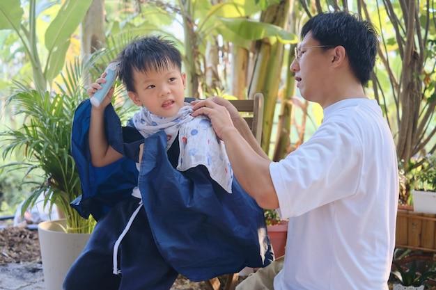 귀여운 아시아 어린 소년이 집에서 머리를 자르고, 아버지는 봉쇄 기간 동안 아들을 위해 머리를 자른다