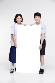 Cute asian kids in student's uniform with white board.