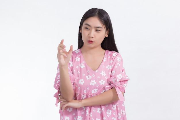 ピンクのドレスを着たかわいいアジアの女性は、白い背景の上に何かを提示または保持するために彼女の手を示しています。