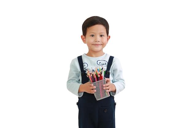 흰색 배경에 격리된 색연필 바구니를 들고 있는 4살 된 귀여운 아시아 소년. 클리핑 패스가 있는 이미지