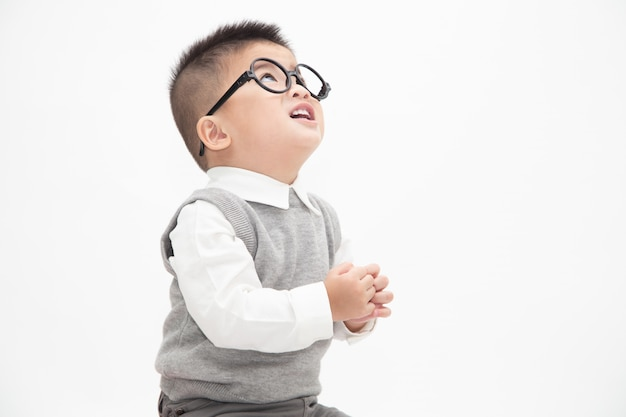 Cute asian little boy wearing white shirt, grey vest and glasses isolated. creative ideas and innovation technology education concept