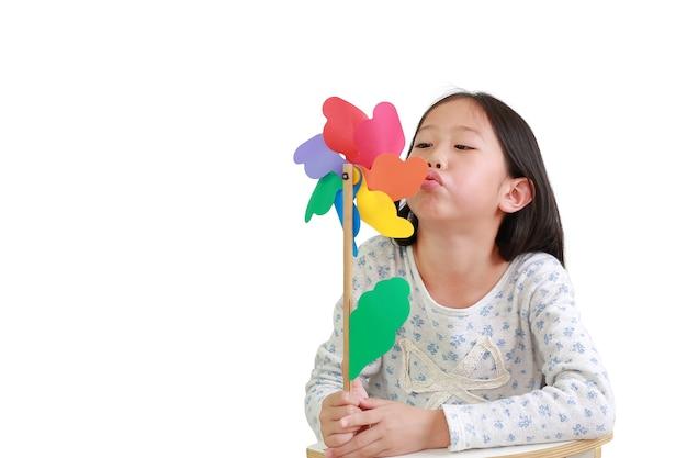 かわいいアジアの小さな子供の女の子が白い背景で隔離のカラフルな風車を吹いています。風車を手に持って遊ぶ子供