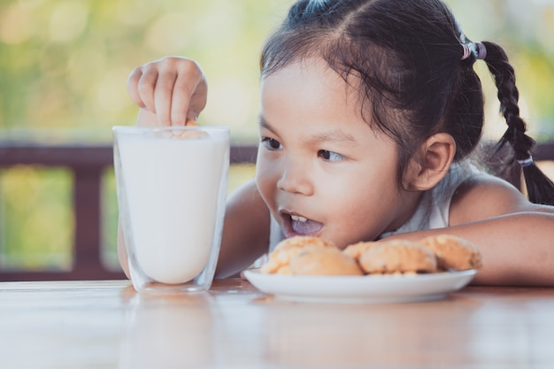 Cute asian little child girl eating cookie with milk for breakfast