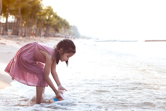 Cute asian little child girl having fun to play on beach in summer vacation