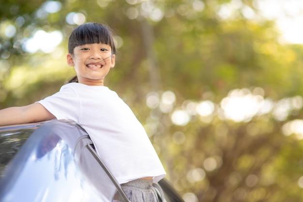 Симпатичная азиатская маленькая девочка с удовольствием путешествует на машине и смотрит из окна ar в сельской местности