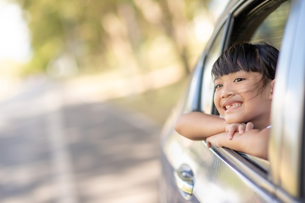Cute asian little child girl having fun to travel by car and looking out from ar window in cthe countryside