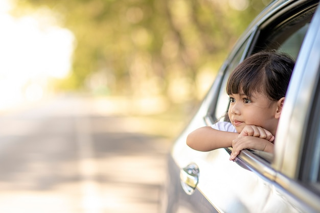 Cute asian little child girl having fun to travel by car and looking out from a window