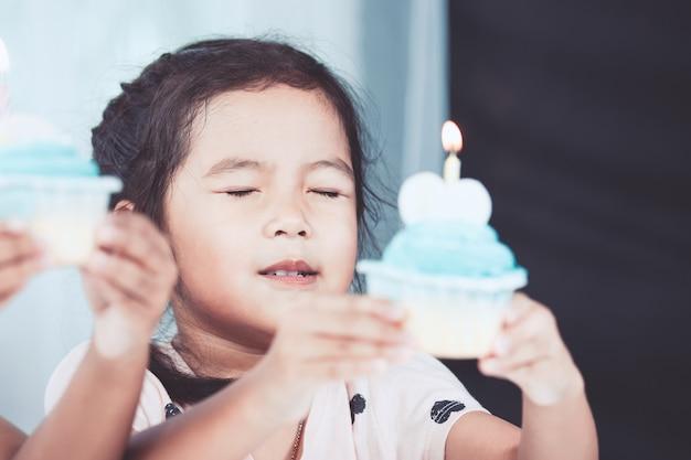 생일 컵 케이크를 들고 귀여운 아시아 작은 아이 소녀와 그녀의 생일에 좋은 일을 기원합니다