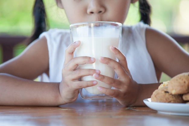 Cute asian little child girl is drinking a milk from glass with cookies
